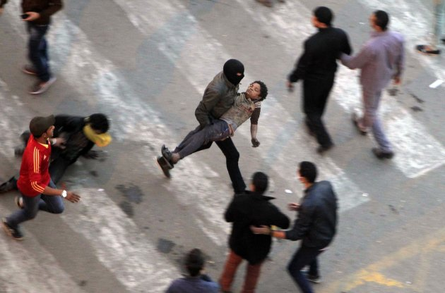Protesters flee from tear gas fired by riot police during clashes at Qasr al-Aini Street near Tahrir Square in Cairo