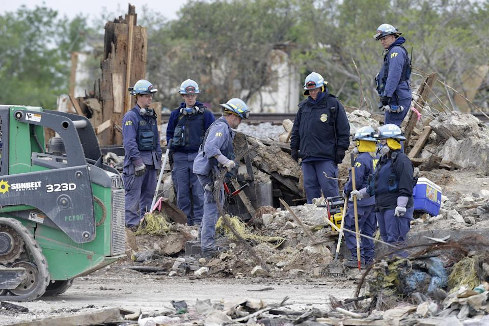 Investigators pause while sifting through the debris of the destroyed fertilizer plant in West, Texas, Thursday, May 2, 2013. Investigators face a slew of challenges in figuring out what caused the explosion at the fertilizer plant that killed 14 people and destroyed part of the small Texas town. (AP Photo/LM Otero, Pool)