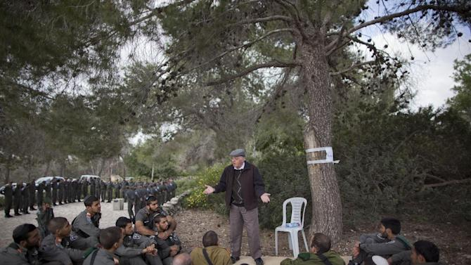 A Holocaust survivor tells his personal testimony to Israeli border police officers during a ceremony marking the annual Holocaust remembrance day a in the Martyr's forest near Moshav Kesalon, in central Israel, Thursday, April 19, 2012. Sirens sounded across Israel on Thursday morning, bringing life to a standstill as millions of Israelis observed a moment of silence to honor the memory of the 6 million Jews killed in the Holocaust of World War II. (AP Photo/Oded Balilty)