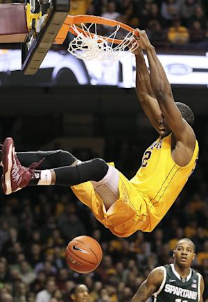 Minnesota forward Trevor Mbakwe dunks in front of Michigan State guard Keith Appling in the second half of an NCAA college basketball game, Monday, Dec. 31, 2012, in Minneapolis. Minnesota won 76-63. (AP Photo/Andy Clayton King)