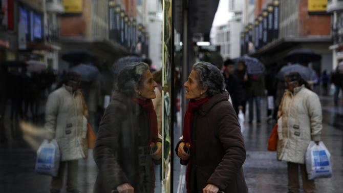 A woman window shops in a commercial district in central Madrid