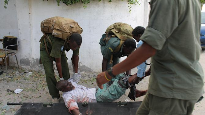 Somali soldiers carry a wounded civilian at the entrance of Mogadishu's court complex after being injured during a siege by militants in Mogadishu, Somalia, Sunday, April 14, 2013. Militants launched a serious and sustained assault on Mogadishu's main court complex Sunday, detonating at least two blasts, taking an unknown number of hostages and exchanging extended volleys of gunfire with government security forces, witnesses said. (AP Photo/Farah Abdi Warsameh)