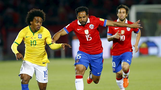 Willian of Brazil controls the ball past Jean Beausejour and Valdivia of Chile during their 2018 World Cup qualifying soccer match in Santiago
