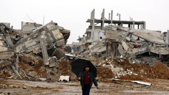 A Kurdish boy walks past damaged buildings in the northern Syrian town of Kobani