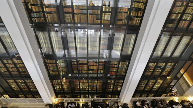 "In this photo taken Wednesday, April 3, 2013, people work on their computers as old books kept at the British Library are displayed, in London. Capturing the unruly, ever-changing Internet is like trying to pin down a raging river. But the British Library is going to try. For centuries the library has preserved a copy of every book, pamphlet, magazine and newspaper published in Britain. Starting Saturday, April 6, 2013, it will also be bound to record every website, e-book and blog, in a bid to preserve the nation's ""digital memory."" (AP Photo/Lefteris Pitarakis)"