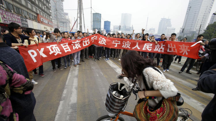 "Protesters march with a banner which reads ""Project PX get out of Ningbo, Ningbo people stand up""  in Zhejiang province's Ningbo city, protesting the proposed expansion of a petrochemical factory Sunday, Oct. 28, 2012. Thousands of people in the eastern Chinese city clashed with police Saturday while protesting the proposed expansion of the factory that they say would spew pollution and damage public health, townspeople said. (AP Photo/Ng Han Guan)"