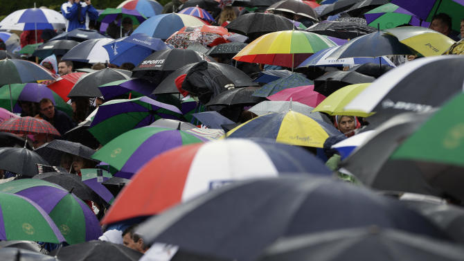 FILE - In this July 8, 2012 file photo, spectators take cover under umbrellas as they gather ahead of Andy Murray of Britain facing Roger Federer of Switzerland during the men's singles final match at the All England Lawn Tennis Championships at Wimbledon, England. Gold, silver, bronze: No matter who wins what at the London Olympics, a million or more visitors will need to get themselves an umbrella. (AP Photo/Alastair Grant, File)
