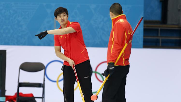 China's Xu Xiaoming, left, gives instructions to skip Liu Rui the 2014 Winter Olympics, Saturday, Feb. 8, 2014, in Sochi, Russia