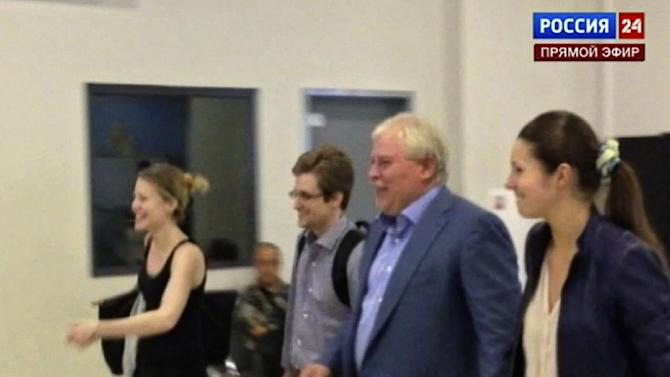 In this video still image taken Thursday, Aug. 1, 2013 and made available Sunday Aug. 4, 2013, by Russia24 TV channel, showing US National Security Agency leaker Edward Snowden, third right, as he leaves Sheremetyevo airport outside Moscow with his Russian lawyer Anatoly Kucherena, second right, on Thursday, Aug. 1, 2013. Snowden has been granted asylum in Russia for one year and left the transit zone of Moscow's airport, his lawyer Kucherena said Thursday while revealing that Snowden's whereabouts will be kept secret for security reasons. (AP Photo/Russia24 via Associated Press Television) TV OUT