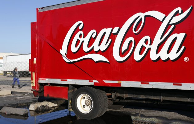A woman walks past a Coca-Cola truck truck at a distribution center in Alexandria