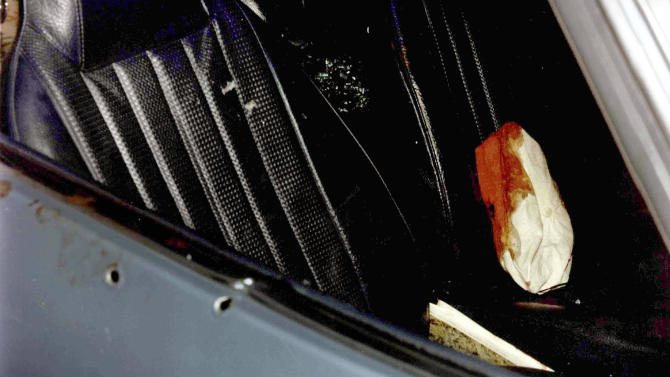 """This undated photo released by the U.S. Attorney's Office and presented as evidence Wednesday, June 19, 2013, during the trial of James """"Whitey"""" Bulger in U.S. District Court in Boston, shows a car with bullet holes in the door and a bloody cap on the seat. Bulger, the reputed former head of the mostly Irish-American Winter Hill Gang based in South Boston, is accused of playing a role in 19 killings during the 1970s and '80s. (AP PhotoU.S. Attorney's Office)"""