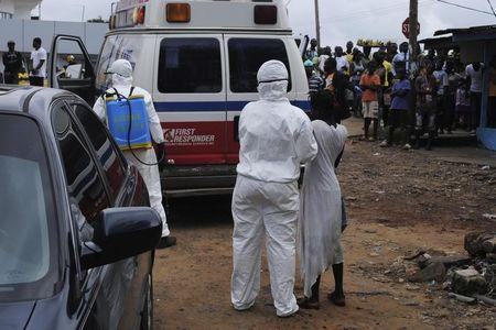 Health workers bring woman suspected of having contracted Ebola virus to an ambulance in front of a crowd in Monrovia