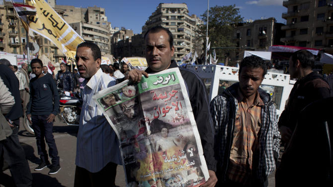"""An Egyptian protester carries a copy of Al Wafd newspaper front page that reads in Arabic """"the brotherhood's crime, no legitimacy for a governor who is against his people,"""" during a protest against President Mohammed Morsi  near the presidential palace, in Cairo, Egypt, Friday, Dec. 7, 2012. Egypt's political crisis spiraled deeper into bitterness and recrimination Friday as thousands of Islamist backers of the president vowed vengeance at a funeral for men killed in bloody clashes earlier this week and large crowds of the president's opponents marched on his palace to increase pressure after he rejected their demands. (AP Photo/Nasser Nasser)"""