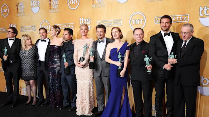 """From left, David O. Russell, Colleen Camp, Alessandro Nivola, Jennifer Lawrence, Michael Pena, Elisabeth Rohm, Jeremy Renner, Amy Adams, Paul Herman, Bradley Cooper and Robert De Niro pose in the press room with the award for outstanding performance by a cast in a motion picture for """"American Hustle"""" at the 20th annual Screen Actors Guild Awards at the Shrine Auditorium on Saturday, Jan. 18, 2014, in Los Angeles. (Photo by Matt Sayles/Invision/AP)"""