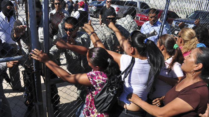 Inmate family members ram the state prison gates demanding information in Ciudad Juarez, Mexico, Tuesday July 26, 2011.  A deadly clash between two rival gangs erupted Monday night at the state prison when a group of prisoners entered the preventive detention area and opened fire on inmates there, said Chihuahua state prosecutors spokesman Carlos Gonzalez. (AP Photo/Raymundo Ruiz)