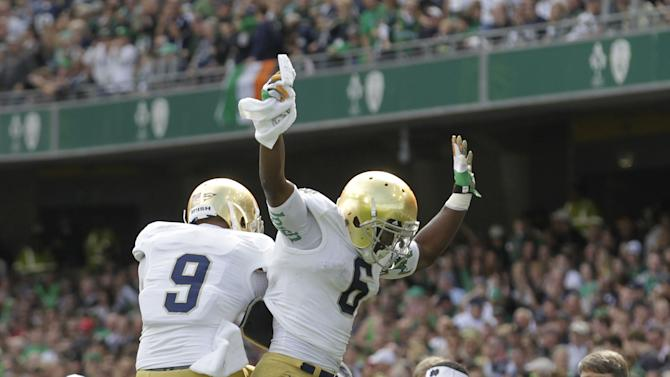 Notre Dame's Theo Riddick, right, reacts with Louis Nix III after scoring a touchdown against the Navy's during their  NCAA college football game  in Dublin, Ireland, Saturday, Sept. 1, 2012.  (AP Photo/Peter Morrison)