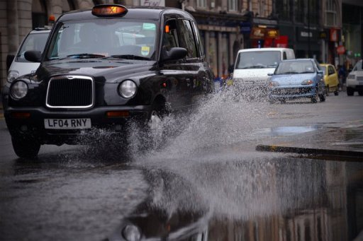 <p>A taxi drives throgh a puddle left by persistent rain in central London in June 2011. The company that makes London's iconic black taxis collapsed into administration on Monday but was hopeful of receiving a financial rescue amid reports of a possible Chinese lifeline.</p>