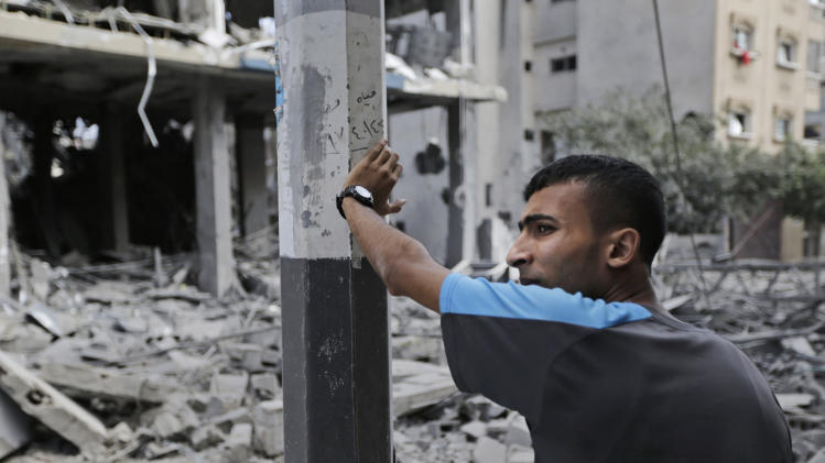 A Palestinian inspects the damage to the offices of the Hamas movement's Al-Aqsa satellite TV station, in Gaza City, northern Gaza Strip, destroyed by an Israeli strike, Tuesday, July 29, 2014. Early Tuesday, Israel warplanes struck a series of targets in Gaza City, including the top Hamas leader in Gaza, Ismail Haniyeh's house and government offices, while Gaza's border area with Israel was hit by heavy tank shelling. (AP Photo/Lefteris Pitarakis)