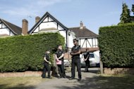 British police stand outside the Claygate, southeast England, home of a family shot dead in their car in the French Alps. A four-year-old girl who survived the shooting returned to Britain Sunday as her wounded elder sister emerged from a coma
