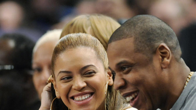 FILE - In this Feb. 20, 2012 file photo, entertainer Jay-Z reacts with his wife, Beyonce, during the third quarter of an NBA basketball game between the New York Knicks and New Jersey Nets, at Madison Square Garden in New York. Beyonce will battle her husband for video of the year at the BET Awards, and now both performers are confirmed to attend, The Associated Press reports Friday, June 29, 2012. Beyonce is the second most nominated act. She's up for six awards. Jay-Z is nominated for five. (AP Photo/Bill Kostroun, File)