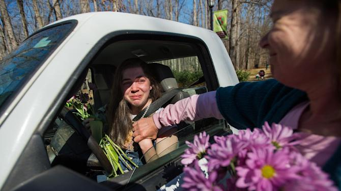In this March 15, 2015 photo, alumni Terry Evans, right, consoles junior Katy Drew as the Sweet Briar community welcomes back their students from spring break in Sweet Briar, Va. Virginia's attorney general announced a mediated settlement Saturday, June 20, to keep the college open, using $12 million raised by fiercely determined alumnae to keep the women's college afloat in the upcoming academic year and sweeping out leadership of the 114-year-old school. (Autumn Parry/News & Daily Advance via AP)
