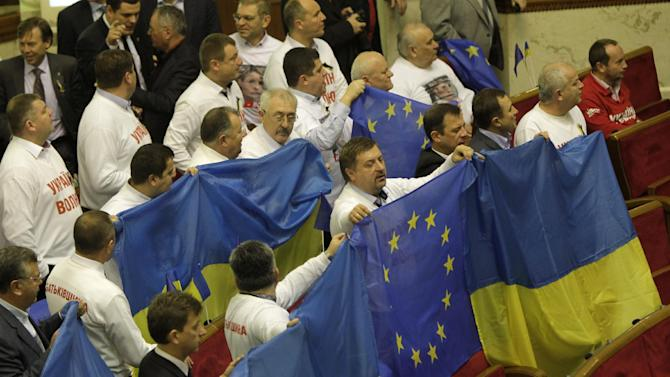 Opposition lawmakers hang Ukrainian and EU flags before a parliament session in Kiev, Ukraine, Friday, Nov. 22, 2013. Opposition lawmakers on Friday booed Ukraine's prime minister, whose government shelved a landmark deal with the European Union, while turning toward Moscow. (AP Photo/Sergei Chuzavkov)