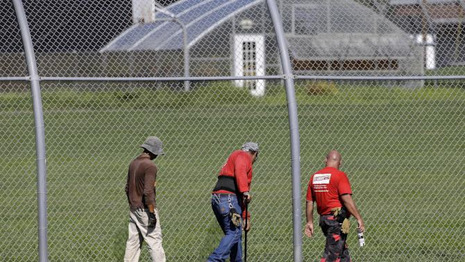 A crew checks for weak spots in the fence surrounding the Woodland Hills Youth Development Center