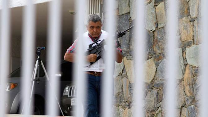 """Retired Venezuelan Army Gen. Angel Vivas, armed and wearing a flak jacket, walks on his property in Caracas, Venezuela, Sunday, Feb. 23, 2014. President Nicolas Maduro ordered on Saturday the arrest and investigation of the retired general for his statements on YouTube and Twitter. Maduro said Vivas is instigating violence at a time when two weeks of anti-government protests have left 10 dead and over 100 wounded. Vivas has been an opponent of the Venezuelan government since his 2007 resignation as director of the Ministry of Defense Engineering, due to the military's adoption of the slogan """"Fatherland, socialism or death, we shall overcome,"""" created in Cuba. (AP Photo/Juan Manuel Hernandez)"""