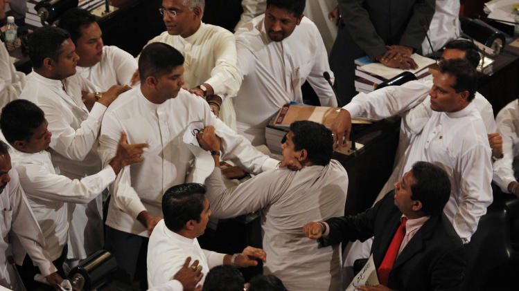 Sri Lanka's ruling party lawmakers, left, scuffle with opposition lawmakers, right, during a budget speech by President Mahinda Rajapaksa in Colombo, Sri Lanka, Monday, Nov. 21, 2011. Opposition lawmakers walked out after the attack. It was not immediately clear whether anyone was injured.(AP Photo/ Eranga Jayawardena)