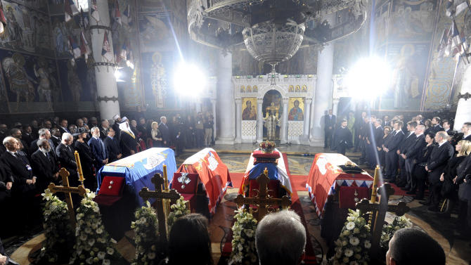 The coffins of King Petar II Karadjordjevic, second from right, his wife Queen Aleksandra, right, mother Queen Maria, third from right, and brother Prince Andrej, left, draped in Serbian royal flags during the funeral ceremony at the St George royal chapel in the town of Topola, Serbia, Sunday, May 26, 2013.  Serbia has held a funeral for Yugoslavia's last king, Peter II Karadjordjevic, who fled the country at the start of World War II and died 1970 in exile aged 47 in the U.S., never returning to Yugoslavia because Communists took over the country at the end of the war.  The former king's remains, and those of his wife, mother and brother, were interred in the family tomb at St. George church during a ceremony aired live on state television. (AP Photo)