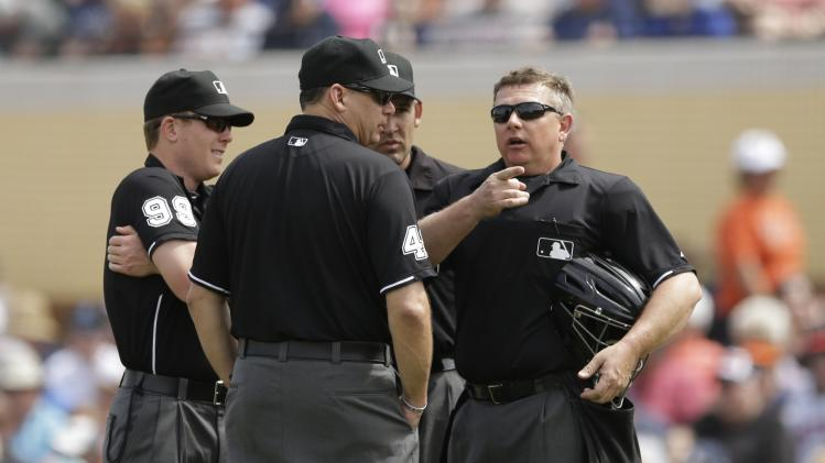 From left, umpires Toby Basner (99), Andy Fletcher (49), Manny Gonzalez, rear center and home plate ump Greg Gibson talk during a spring exhibition baseball game between the Detroit Tigers and the Toronto Blue Jays in Lakeland, Fla., Tuesday, March 11, 2014. (AP Photo/Carlos Osorio)