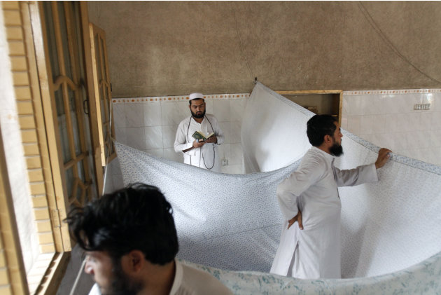 An Afghan Muslim devotee, who lives and  prays in isolation in a mosque during  Itikaf, the last ten days of the Islamic fasting month of Ramadan, reads from the Quran in the city of Jalalabad east of
