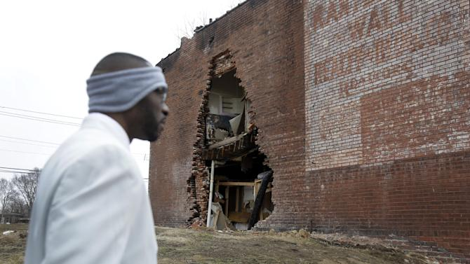 In this Thursday, Jan. 16, 2014 photo, Melvin White, founder of the Beloved Streets of America project, walks past crumbling building during a tour of Dr. Martin Luther King Jr. Drive in St. Louis. The nonprofit is working to revitalize a downtrodden six-mile stretch of the drive named for the slain civil rights leader, marked by vacant lots, crumbling buildings and a preponderance of liquor stores, pawn shops and check-cashing businesses. Project leaders hope revitalize MLK's streets that have fallen into disrepair in cities around the country. (AP Photo/Jeff Roberson)