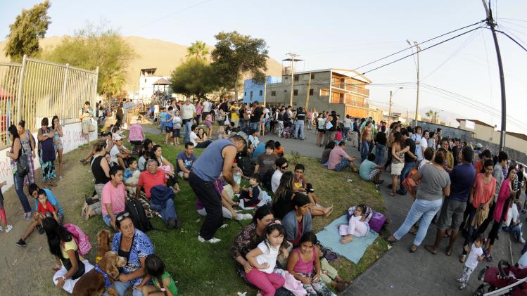 People stay on higher grounds in a tsunami safety zone after a magnitude 6.7 earthquake shook the region, in Iquique city, north of Santiago