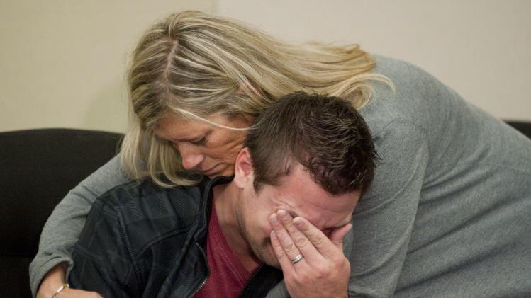 GRESHAM, OREGON - October 18, 2012 -  Clint Heichel gets a hug from Lorilei Ritmiller, mother of Whitney Heichel, as he breaks down after he attempted to speak at a news conference Thursday Oct. 18, 2012 in the council chambers for the City of Gresham. (AP Photo/Brent Wojahn, The Oregonian)