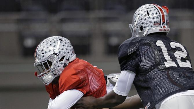 Ohio State quarterback Cardale Jones (12) hands off to running back Ezekiel Elliott during NCAA college football practice at the Mercedes-Benz Superdome in New Orleans, La., Sunday, Dec. 28, 2014. Ohio State is scheduled to play Alabama in the Sugar Bowl on Jan. 1, 2015. (AP Photo/Gerald Herbert)
