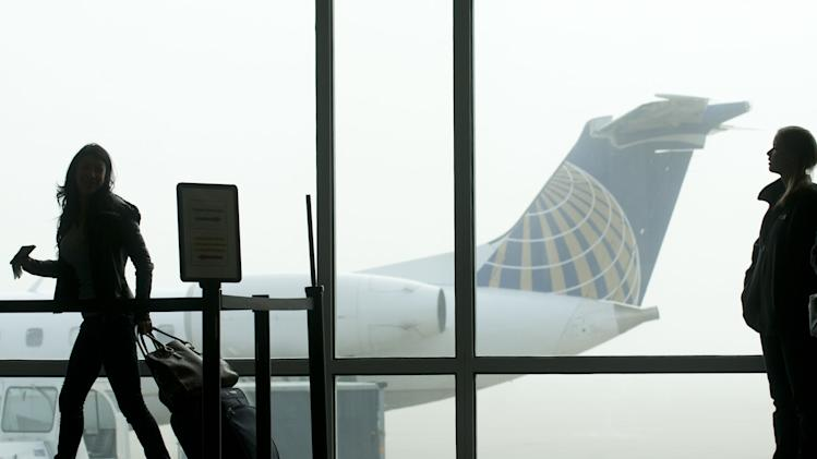 Thanksgiving weekend travelers at Grand Rapids, Michigan's Gerald R. Ford Airport are delayed by fog, Wednesday, Nov. 21, 2012. (AP Photo/The Grand Rapids Press, Chris Clark)