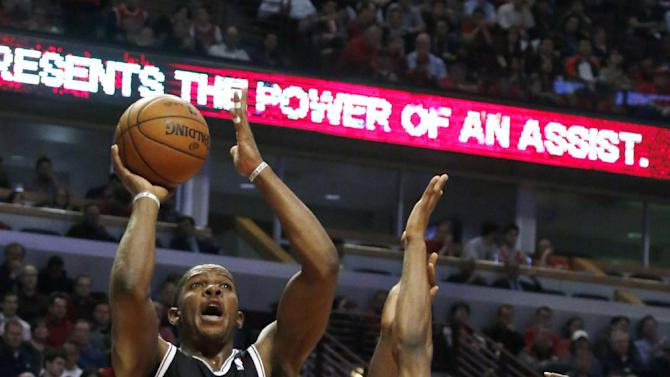 Brooklyn Nets guard Joe Johnson (7) shoots over Chicago Bulls' Jimmy Butler (21) and Nazr Mohammed during the first half of Game 3 of their first-round NBA basketball playoff series, Thursday, April 25, 2013, in Chicago. (AP Photo/Charles Rex Arbogast)