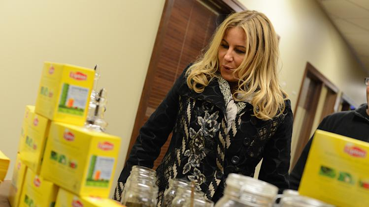 IMAGE DISTRIBUTED FOR LIPTON: Actress Jennifer Coolidge gets excited over creating her own custom brew at the Lipton Uplift Lounge Tea Bar during Sundance on Sunday Jan. 20, 2013, in Park City, UT. (Photo by Jordan Strauss/Invision for Lipton/AP Images)
