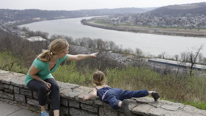 This April 10, 2013 photo shows Rachel Mardis pointing out over the Ohio River towards northern Kentucky with her daughter Skylar, 2, at the Eden Park Overlook in Cincinnati. A beautiful stroll in Cincinnati begins in lovely Eden Park and ends atop Mount Adams. (AP Photo/Al Behrman)
