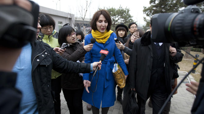 """In this Thursday, March 22, 2012 photo, Kim Lee, center, wife of """"Crazy English"""" founder Li Yang, is surrounded by local journalists as she walks into a court for her divorce trial in Beijing, China. Lee's case has opened the door to a torrent of anguish about domestic violence in her adopted country, and she has became a folk hero for battered Chinese women. In China, where tradition holds that family matters are private and women are in many ways subservient to their husbands, the American woman's case has spawned tens of thousands of postings on Twitter-like sites, along with protests and talk show debates. It is especially explosive because she is a foreigner, at a time when China is particularly sensitive about how it is understood and treated by the world. (AP Photo/Alexander F. Yuan)"""