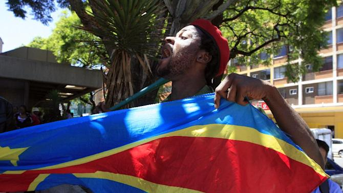 A supporter holds a Democratic Repupublic of Congo flag outside the court in Pretoria, South Africa, on Thursday, Feb. 7, 2013. Nineteen alleged members of a Congolese rebel group — including one U.S. citizen — sought help in their effort to overthrow Congolese President Joseph Kabila, offering mining rights in their resource-rich country in exchange for weapons and training, a prosecutor said Thursday. (AP Photo/Jon Gambrell)