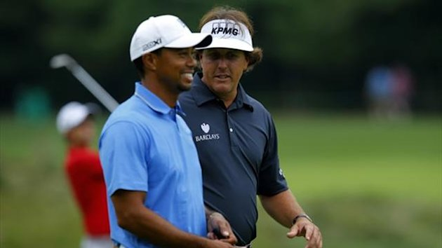 Tiger Woods (L) and Phil Mickelson, both of the United States, walk up the sixth fairway during the first round of the Deutsche Bank Championship (Reuters)