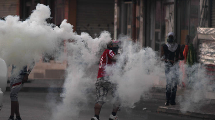 A Bahraini anti-government protester runs through tear gas fired by riot police during clashes after a march to recognize protesters who have lost their vision after being shot in the eye with bird shot, rubber bullets or tear gas canisters during past clashes Thursday, June 7, 2012, in Sitra, Bahrain. (AP Photo/Hasan Jamali)