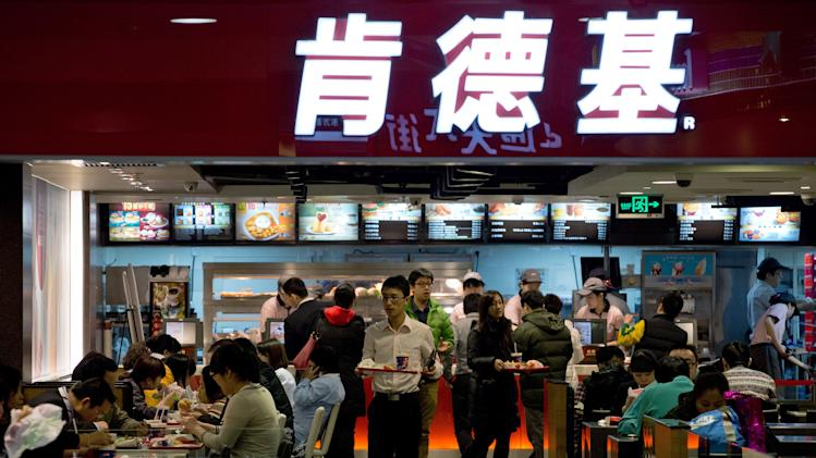Customers buy meals at a KFC restaurant at a shopping mall in Beijing Monday, Feb. 25, 2013. KFC launched a campaign Monday to rebuild its battered brand in China, promising tighter quality control after a scandal over misuse of drugs by its poultry suppliers. (AP Photo/Andy Wong)