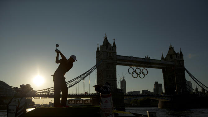 U.S. golfer Dustin Johnson is silhouetted as he takes a swing in a posed picture for photographers as Olympic rings hang from Tower Bridge ahead of the 2012 Summer Olympics, Monday, July 23, 2012, in London.  Johnson and Spanish golfer Sergio Garcia took it in turns to hit golf balls at a floating golf hole on the River Thames to promote for a sportswear maker.  Golf is set to be included as an Olympic sport in the next games in 2016.  (AP Photo/Matt Dunham)