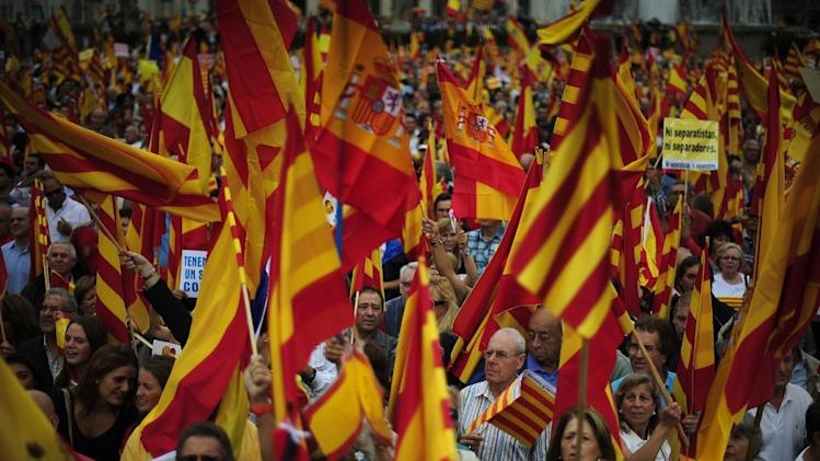 People opposed to the independence of Catalonia hold Catalan and Spanish flags during the holiday known as Dia de la Hispanidad, Spain's National Day in Barcelona, Spain, Friday, Oct. 12, 2012. Spain is observing its National Day festivities in somber mood as the traditional military pageant was scaled back to cut costs. Spain is in recession and under pressure to fix its finances while celebrating the day Christopher Columbus discovered America in the name of the Spanish Crown. (AP Photo/Manu Fernandez)