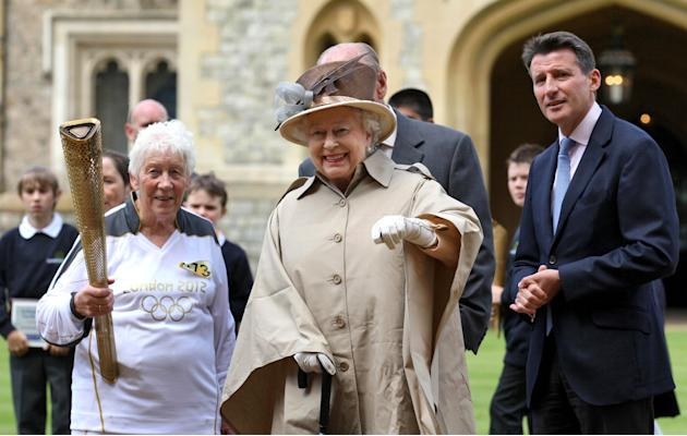 This image made available by LOCOG shows Queen Elizabeth II, center, and the Duke of Edinburgh, obscured, and Olympic chairman Sebastian Coe right, watch as Torchbearer 073 Gina Macgregor, left, holds