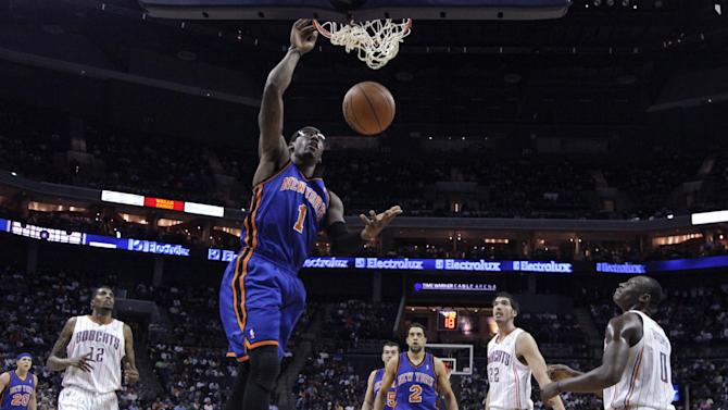 New York Knicks' Amare Stoudemire (1) dunks as Charlotte Bobcats' Tyrus Thomas (12), Byron Mullens (22) and Bismack Biyombo (0) watch during the first half of an NBA basketball game in Charlotte, N.C., Thursday, April 26, 2012. (AP Photo/Chuck Burton)