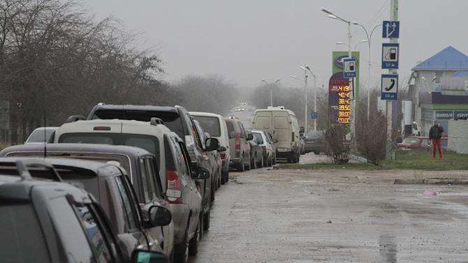 Cars queue up outside a petrol station as the drivers wait to buy additional supplies of fuel in Yevpatoriya